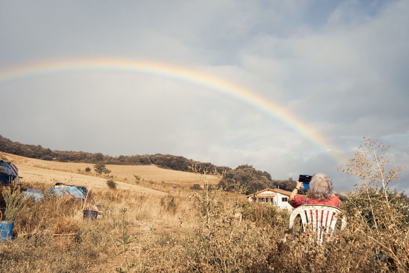Rear view of people sitting on field against rainbow in sky