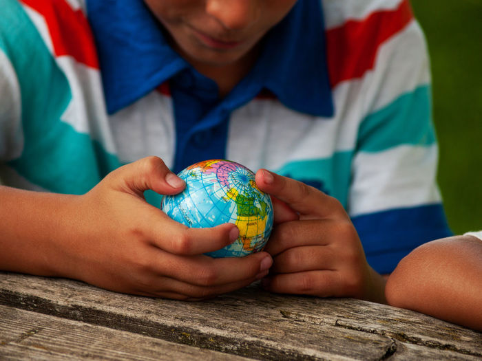 Midsection of boy looking at globe on table