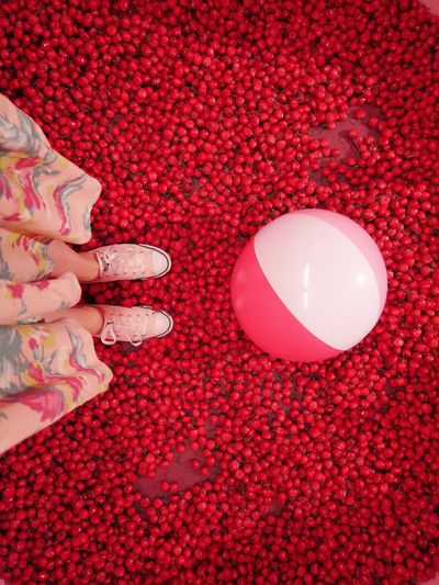 Low section of woman with ball standing on cherries