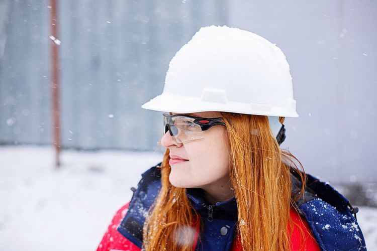 Portrait of woman worker in overalls wearing hat against snow