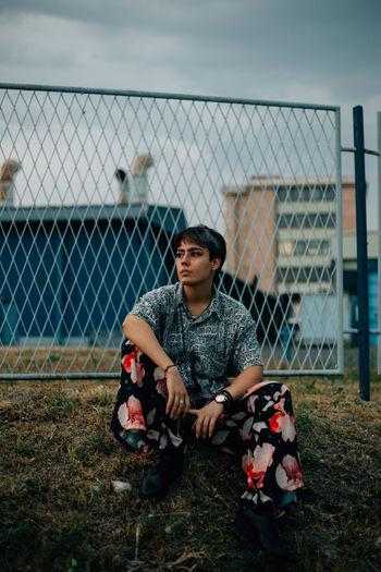 Full length of boy sitting by fence