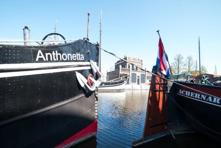 Ships and architecture Nautical Vessel Text Transportation Mode Of Transportation Water Western Script Flag Communication Sky Nature Day Moored Patriotism No People Architecture Travel Outdoors River Passenger Craft