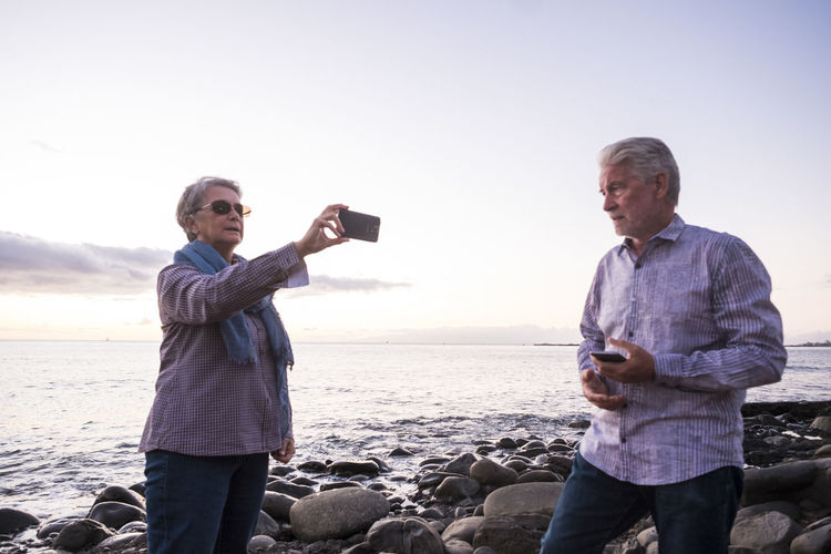 senior couple white and grey hair, mobile technology, front of ocean Beach Camera - Photographic Equipment Communication Holding Mobile Phone Nature Photo Messaging Photographing Photography Themes Portable Information Device Rock Beach Sea Selfie Senior Couple Sky Smart Phone Standing Sunset Technology Togetherness Two People Vacations Wireless Technology