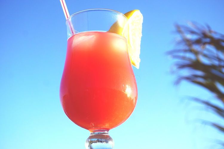 tropical drink against blue sky Drink Cocktail Cocktails Blue Sky Summer Relax Drinks Cocktail Glass Tequila - Drink Tequila Sunrise Red Drinking Straw Lemon Slice