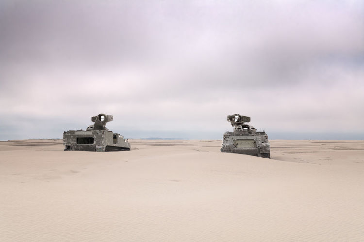 2 army tanks on the beach with bullet holes