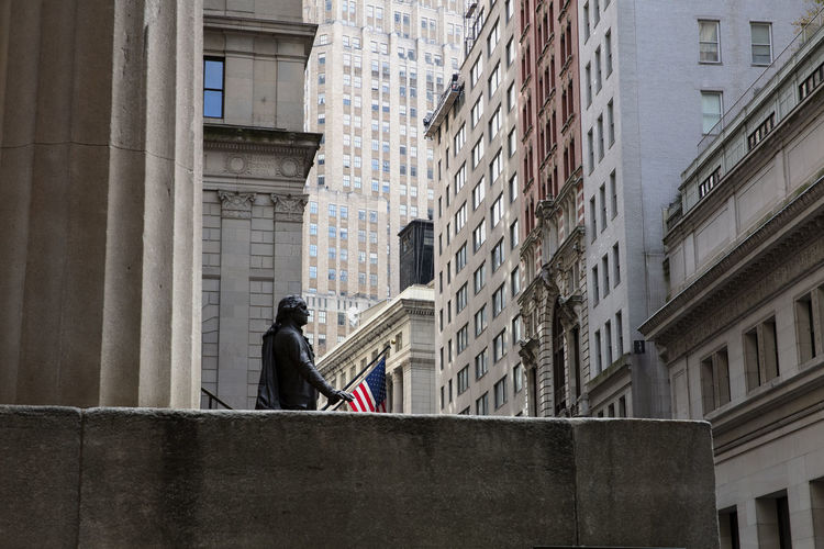 Rear view of man standing against buildings in city