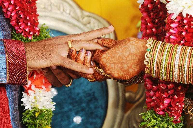 Cropped Hands Of Bride And Bridegroom Exchanging Rings