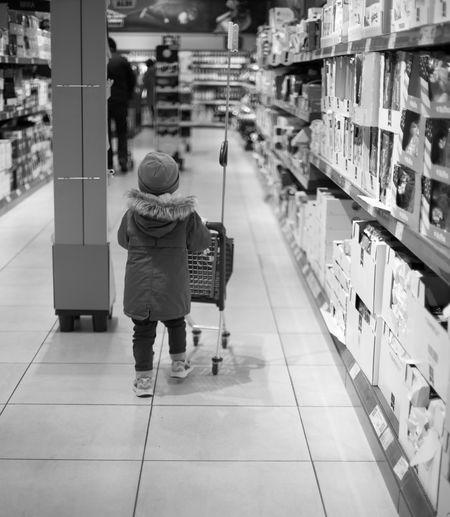 Full length rear view of boy walking at store