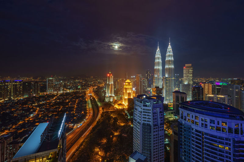 Illuminated petronas towers amidst cityscape against sky at night