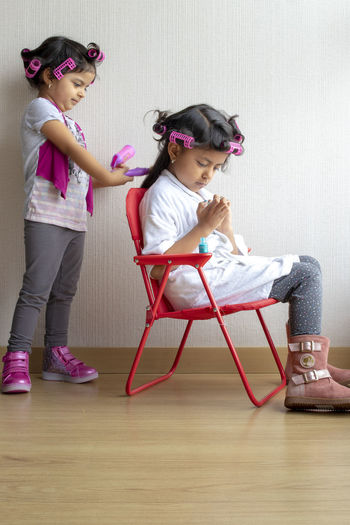 Girl Styling Hair Of Sister Sitting On Chair At Home