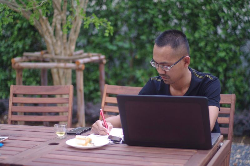 Man writing in book while sitting at table against plants