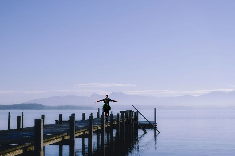 Tranquility at Chiemsee Lake, Germany Sky Water Scenics - Nature Real People Beauty In Nature Lifestyles One Person Standing Mountain Tranquil Scene Tranquility Leisure Activity Non-urban Scene Rear View Human Arm Arms Raised Wooden Post Pier Lake Chiemsee 17.62°