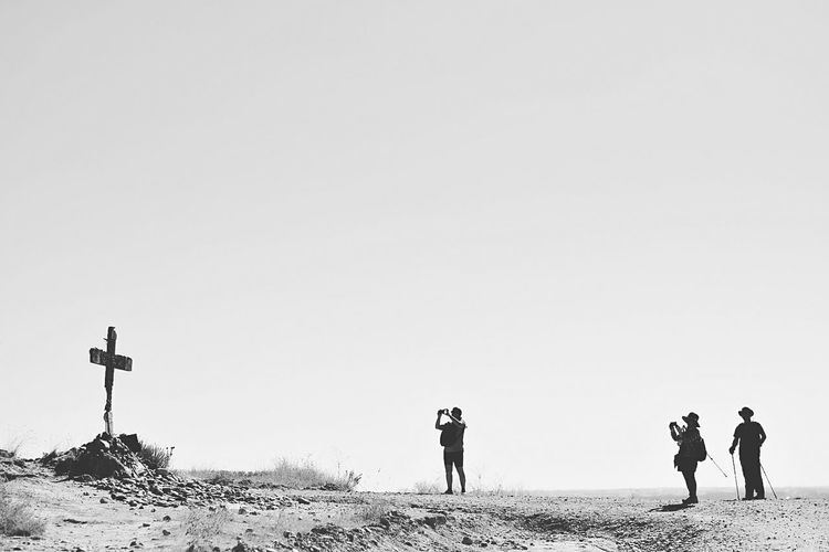 Side view of men photographing cross in arid landscape