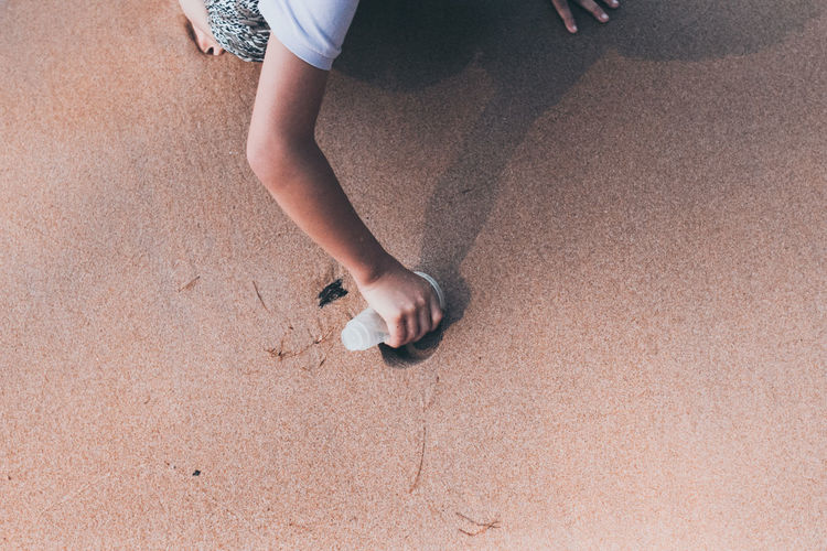 Girl collecting sand in glass at beach