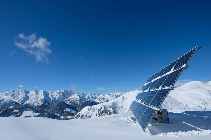 Solar panel on snow covered ground against sky