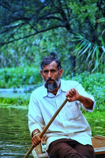 Portrait of man sitting in boat on lake