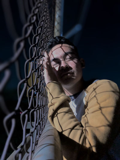 Portrait of young man standing by chainlink fence