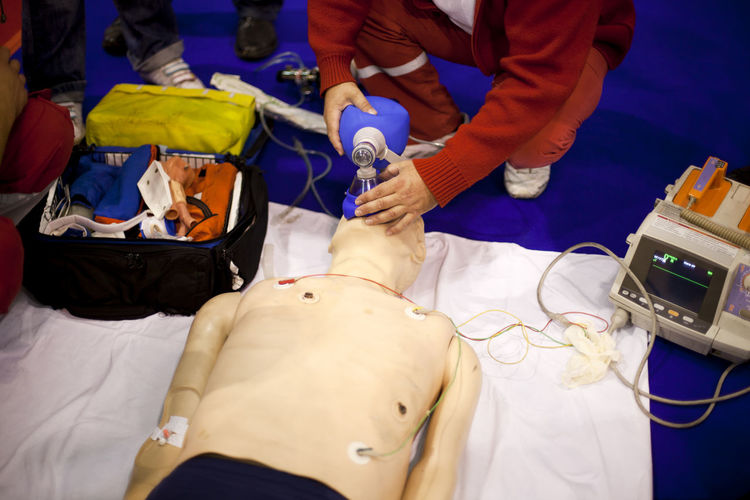 High Angle View Of Healthcare Worker Practicing Mechanical Ventilation On Cpr Dummy