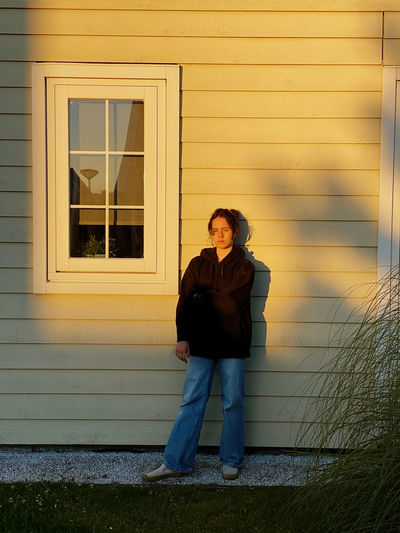 Full length portrait of young woman standing against building
