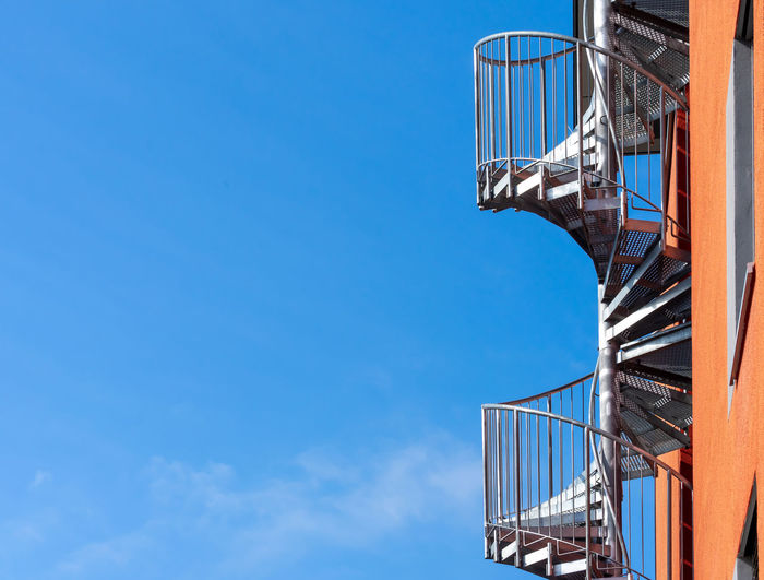 Low angle view of staircase against blue sky