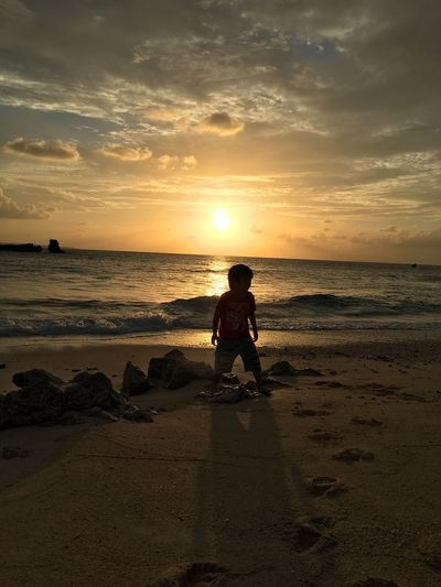 Silhouette Boy At Beach Against Sky During Sunset