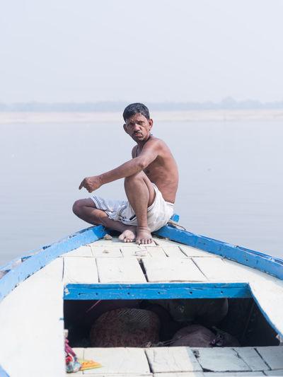 Full length of shirtless man sitting on sea against sky