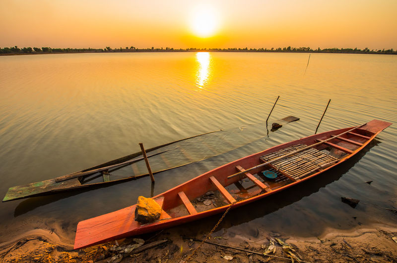 Nautical Vessel Water Mode Of Transportation Sunset Transportation Sky Nature Moored Tranquility Reflection No People Beauty In Nature Tranquil Scene Scenics - Nature Lake Orange Color Outdoors Non-urban Scene Wood - Material Rowboat