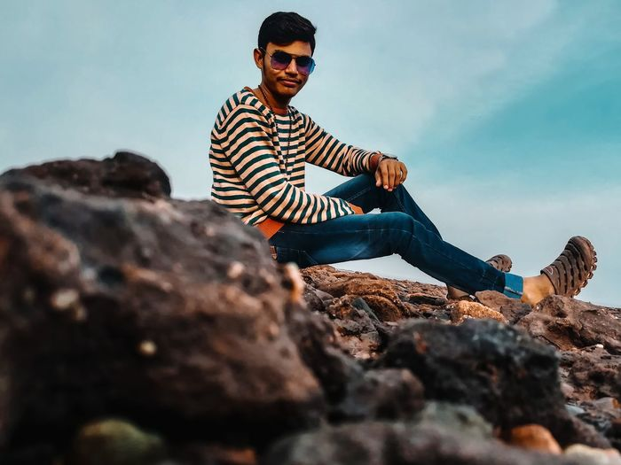 Young man wearing sunglasses on rock against sky