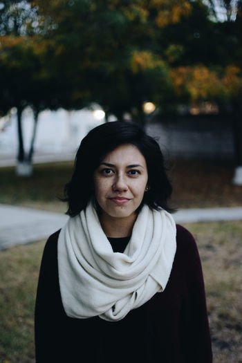 Portrait Of Young Woman Wearing Scarf Standing At Park