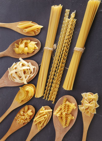 Close-up of raw pasta and wooden spoon on table