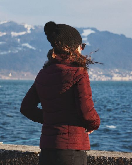 Young woman standing by sea against mountain during winter