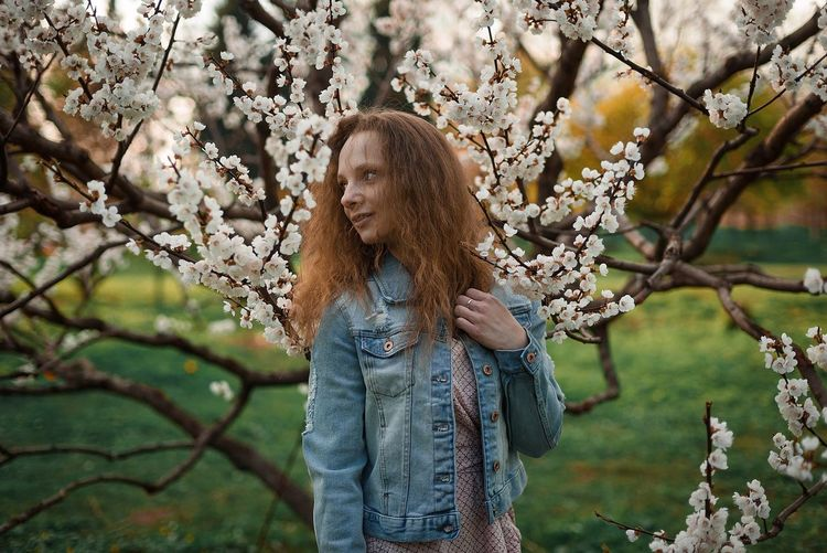 Low angle view of woman standing by cherry tree