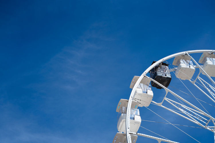 Ferris wheel with white cabins and one black one. diversity and tokenism concept