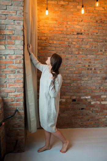 Studio Adult Adults Only Brick Wall Candle Day Domestic Life Fashion Linen Full Length Illuminated Indoors  Leisure Activity Lifestyles Model One Person One Woman Only One Young Woman Only Only Women People Real People Standing Summer Fashion Women Young Adult Young Women