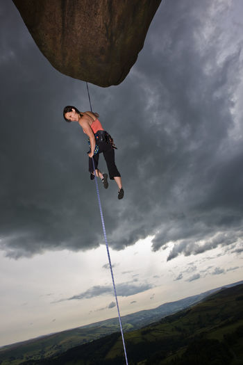 Low angle view of man climbing on mountain against sky