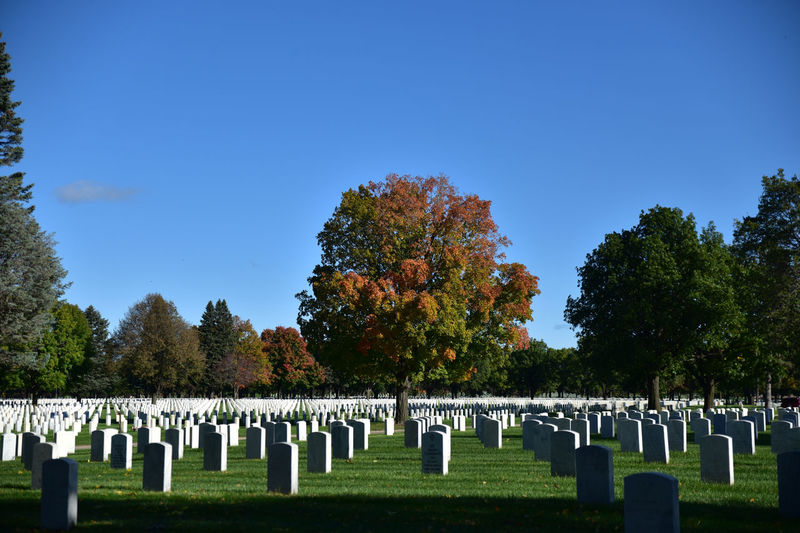Row of tombstones at fort snelling national cemetery against blue sky