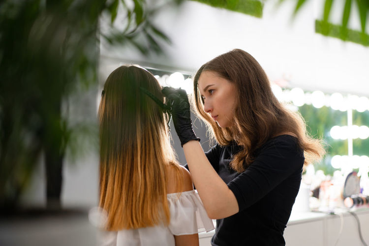 Beautician applying make-up to client