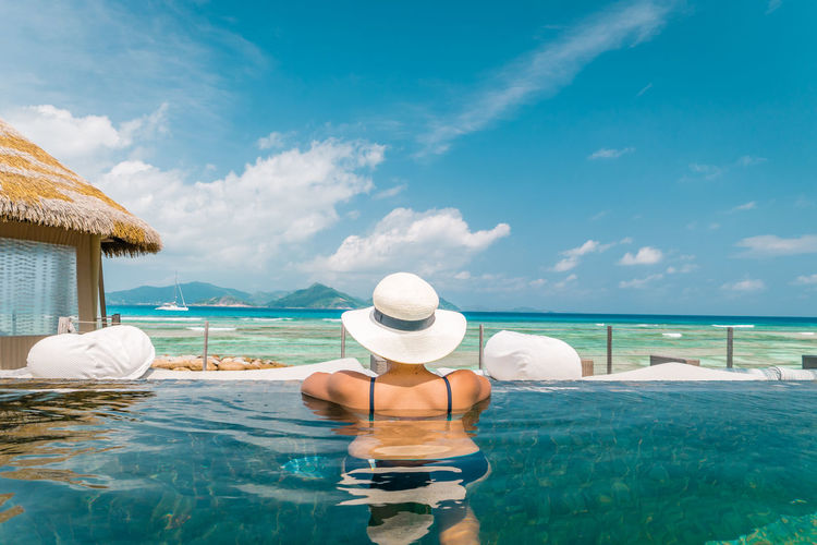 Seychelles tropical island Seychelles Beauty In Nature Clothing Cloud - Sky Day Hat Holiday Horizon Over Water Leisure Activity Lifestyles Luxury Nature One Person Outdoors Real People Rear View Sea Sun Hat Swim Pool Swimming Pool Trip Tropical Island Vacations Water Womans Wim Pool
