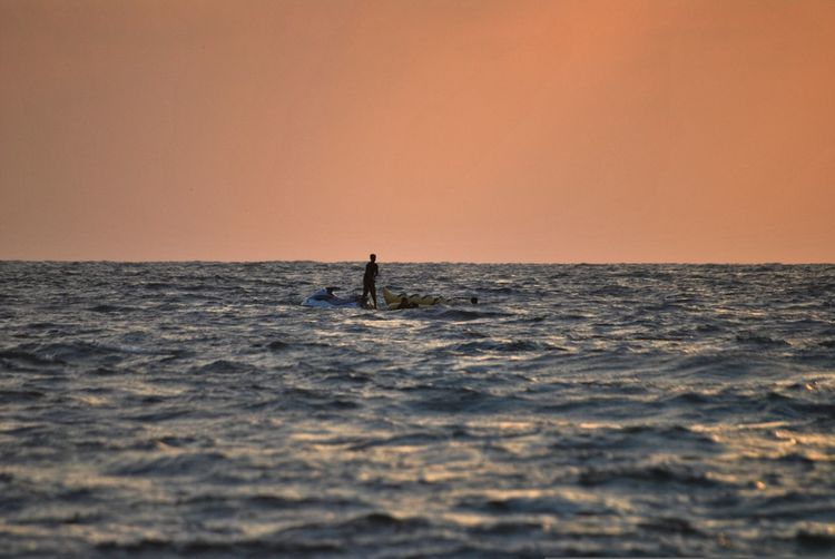 Distant view of man riding on jet boat amidst sea against clear sky during sunset