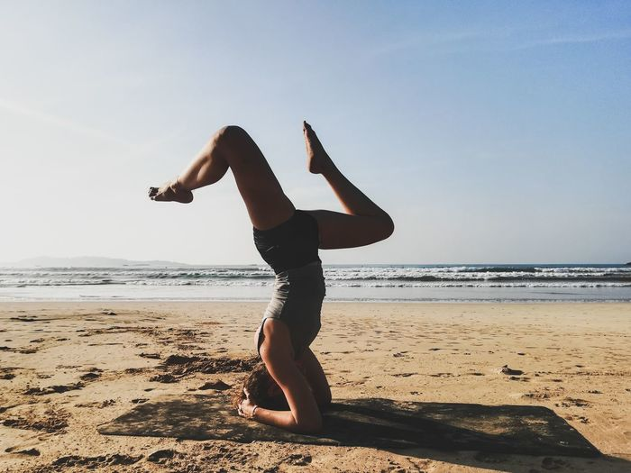 Full length of woman headstand on beach against sky