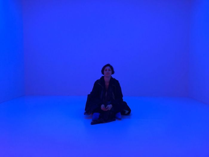 Woman sitting against blue background