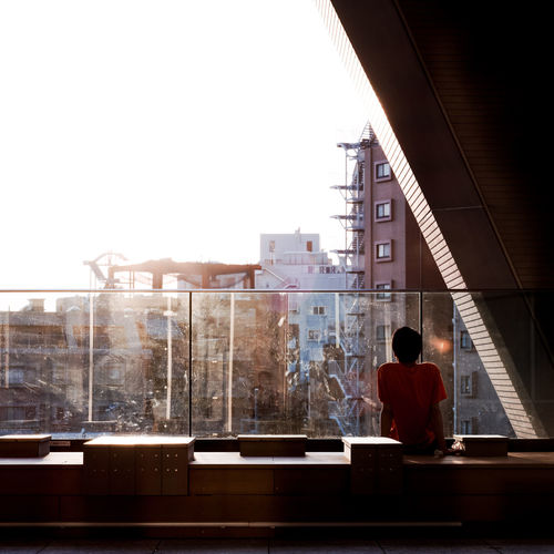 Rear view of man sitting by glass railing