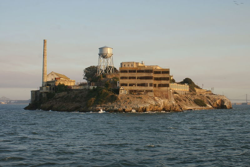 The prison on Alcatraz Island is golden in the late afternoon sun, in San Francisco Bay. Abandoned Abandoned Buildings Architecture Blue Day Golden Hour Historic Historic Building History Island No People Ocean Outdoors Prison Rock San Francisco Bay Sea Unedited Photo Water Water Tower