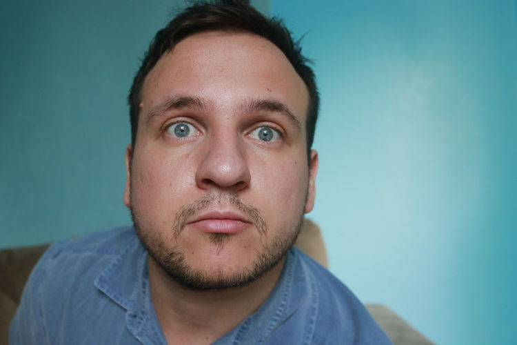 Headshot Portrait Front View One Person Blue Looking At Camera Beard Indoors  Colored Background Blue Background Young Adult Facial Hair Studio Shot Real People Close-up Young Men Lifestyles Men Contemplation Human Face Closeup Scary Scary Face Blue Eyes