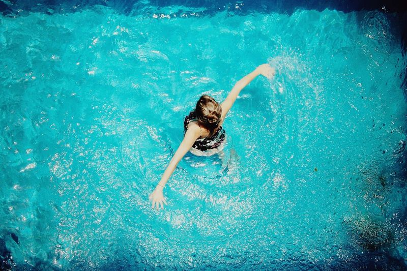 Portrait of young woman swimming in pool