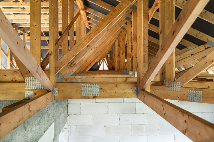 Roof trusses covered with a membrane on a detached house under construction, view from the inside,
