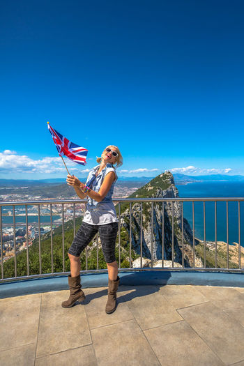 Woman holding flag while standing by railing against sky