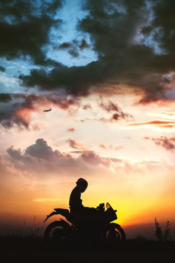 Silhouette man sitting on motorcycle against sky during sunset