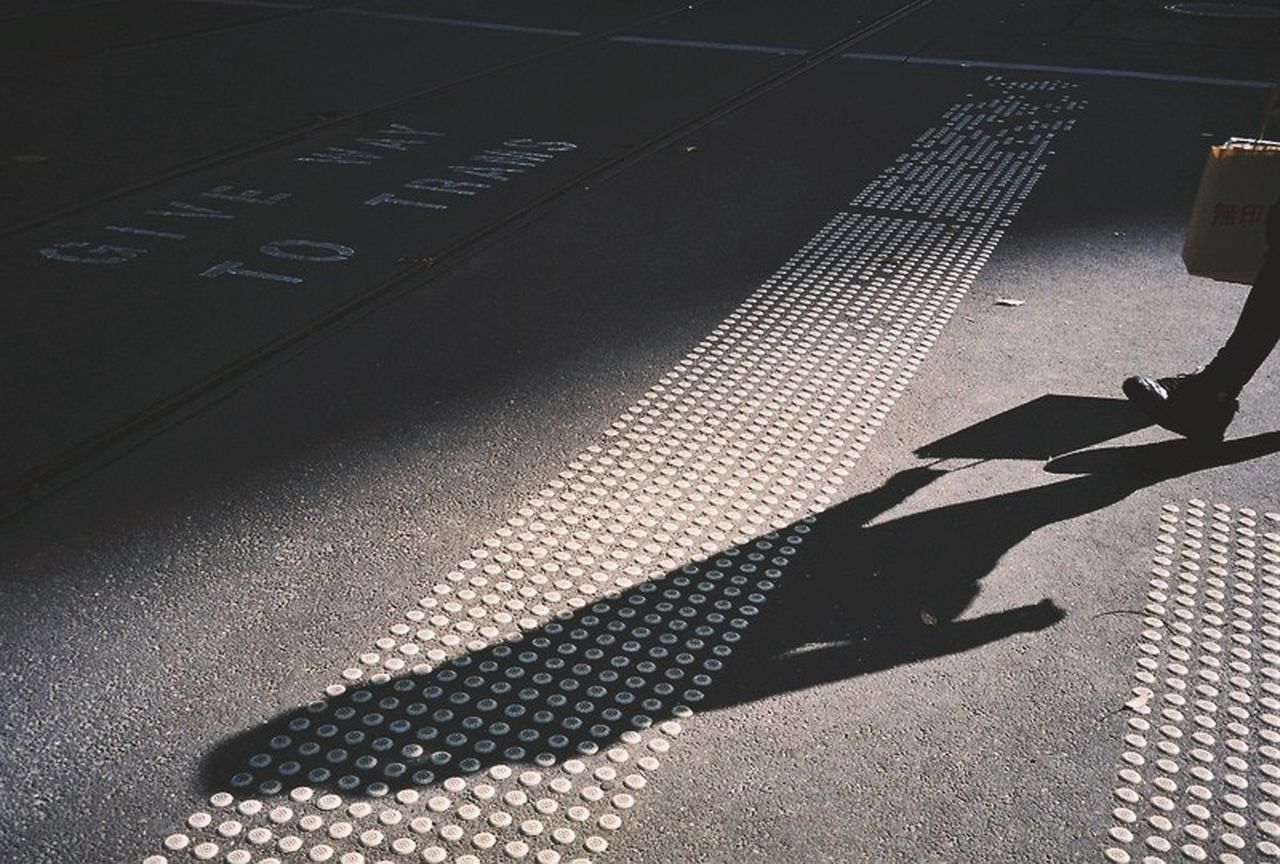 HIGH ANGLE VIEW OF MAN SHADOW ON STREET