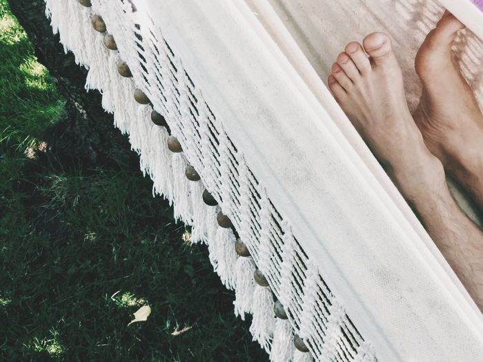 Cropped image of person lying in hammock